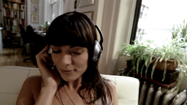 ms woman sitting in chair, putting on headphones, + listening to music/ new york city - young women stock videos & royalty-free footage