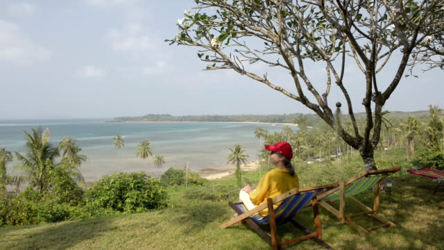woman sitting in deckchair and enjoy beach panorama - gulf of thailand stock videos & royalty-free footage