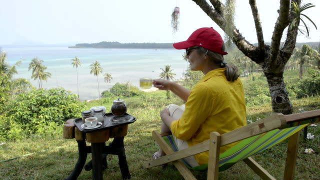 woman sitting in deckchair, drinking tea and enjoy beach panorama - gulf of thailand stock videos & royalty-free footage