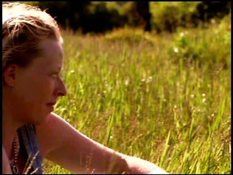 woman sitting in field - endast unga kvinnor bildbanksvideor och videomaterial från bakom kulisserna