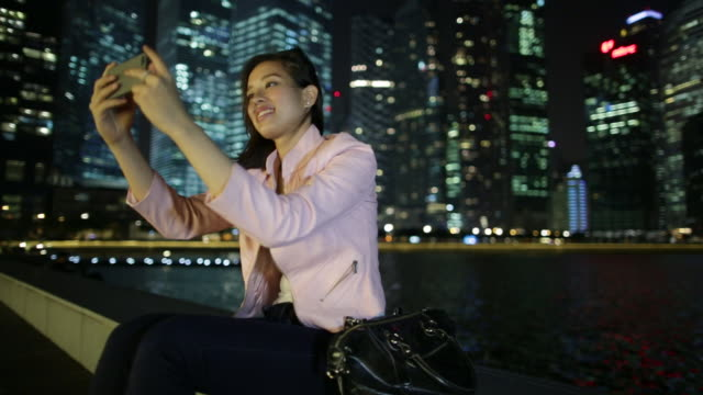 ms woman sitting in front of buildings at night, taking pictures.  - 僅年輕女人 個影片檔及 b 捲影像