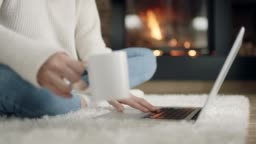 Woman sitting in front of the fireplace, drinking coffee and using laptop
