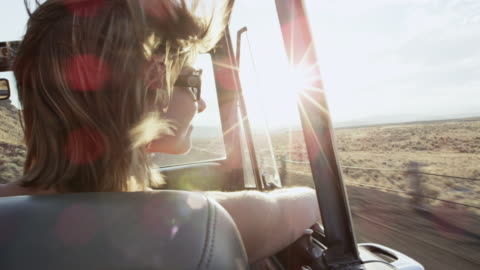ms woman sitting in front seat of convertible off road vehicle looking out at desert landscape - lens flare stock videos & royalty-free footage