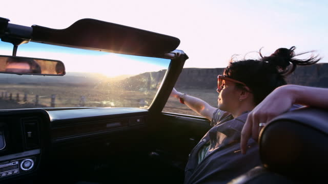 ms woman sitting in front seat of convertible sunset in background/washington, usa  - ドライブ旅行点の映像素材/bロール