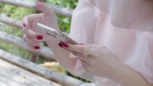 vidéos et rushes de femme assise dans le jardin et à l'aide de téléphone intelligent - seulement des jeunes femmes
