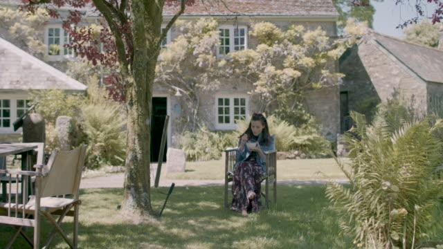 vídeos de stock, filmes e b-roll de woman sitting in garden - jaqueta jeans