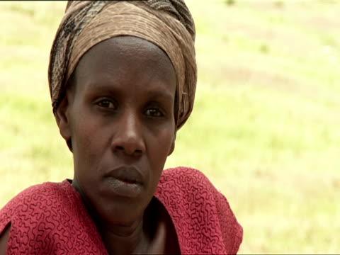cu woman sitting in grass and staring at camera intensely / kigali, rwanda - フツ族点の映像素材/bロール