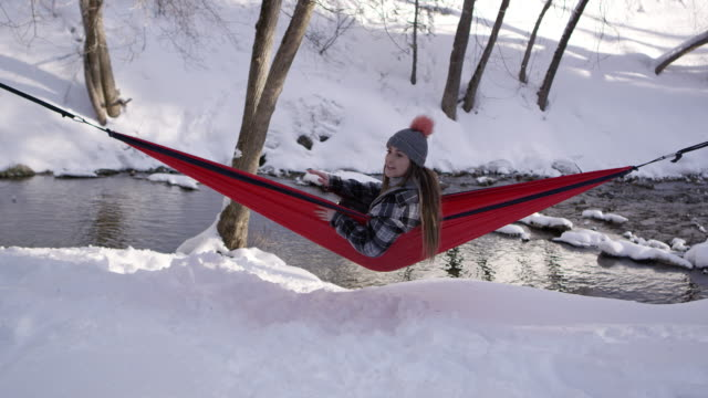 woman sitting in hammock during winter calling dog over - american fork city stock videos & royalty-free footage