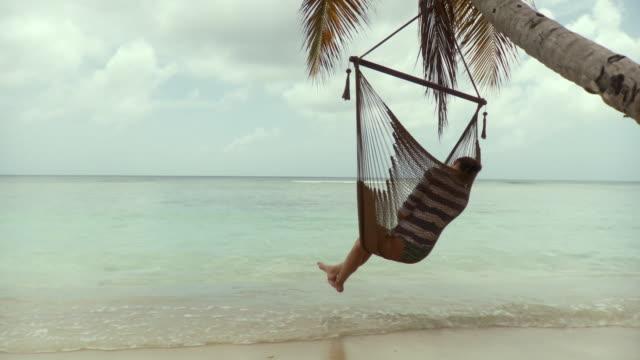 ws woman sitting in hammock on beach / scarborough, tobago, trinidad and tobago - ganzkörperansicht stock-videos und b-roll-filmmaterial