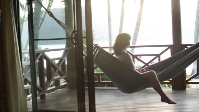 vídeos de stock e filmes b-roll de woman sitting in hammock on veranda enjoying breeze in her hair. - alpendre