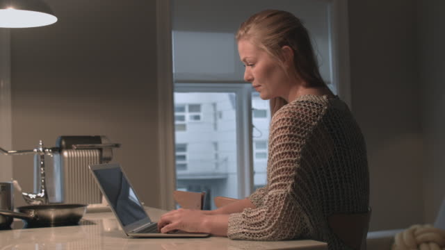 Woman sitting in her appartment working on laptop