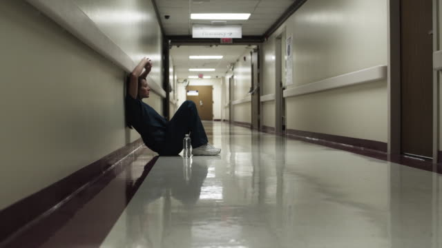 ws woman sitting in hospital corridor / payson, utah, usa - weitwinkelaufnahme stock-videos und b-roll-filmmaterial