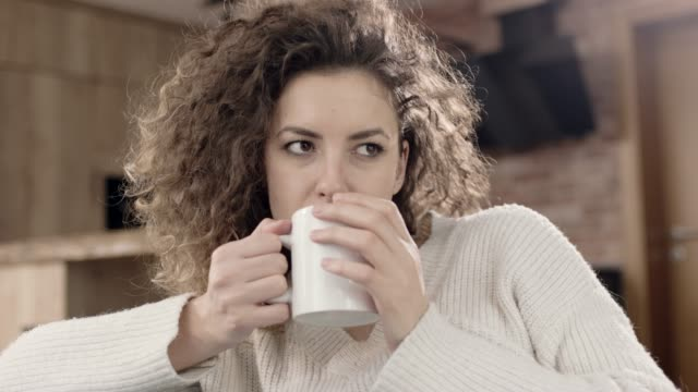 woman sitting in kitchen and drinking coffee - hoozone stock videos and b-roll footage