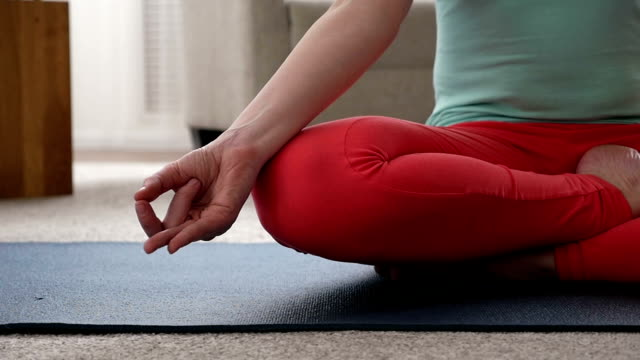 Woman sitting in lotus pose, cropped footage