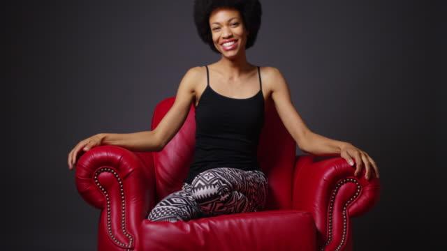 woman sitting in red armchair - stuhl stock-videos und b-roll-filmmaterial