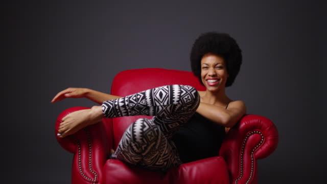 vídeos y material grabado en eventos de stock de woman sitting in red leather armchair - camisola