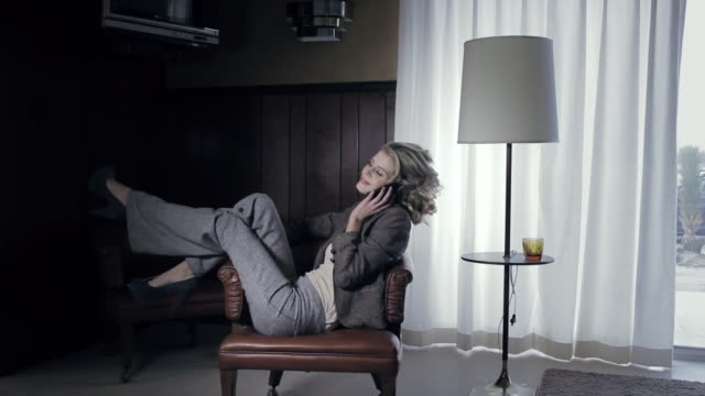 MS Woman sitting in relaxed position in armchair in old fashioned hotel room while playfully tossing up legs and talking on cell phone / Palmdale, CA, United States