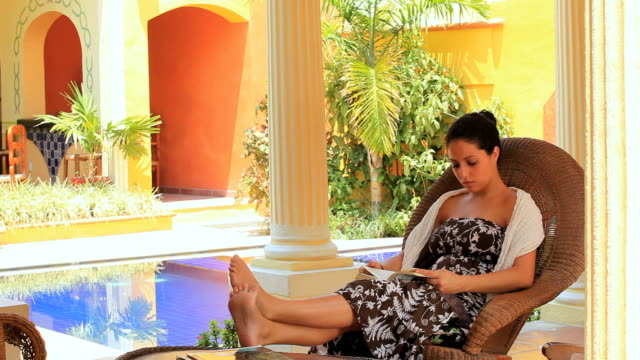 vidéos et rushes de ws woman sitting in rocking chair with feet up on table, reading book, merida, yucatan, mexico - rebord de piscine