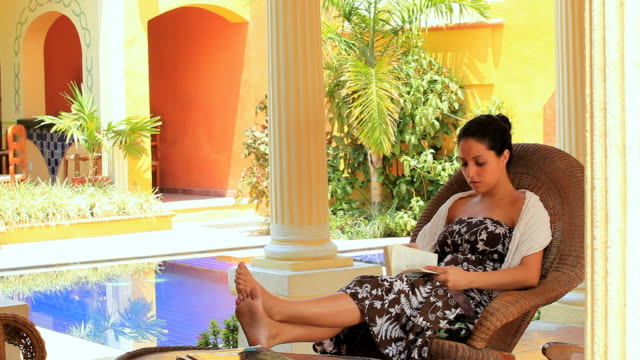 stockvideo's en b-roll-footage met ws woman sitting in rocking chair with feet up on table, reading book, merida, yucatan, mexico - schommelen schommelstoel