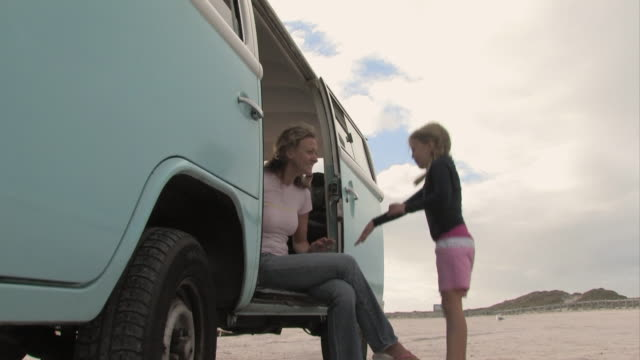 MS, Woman sitting in VW bus giving boogie board to girl (6-7) on beach, Cape Town, Western cape, South Africa