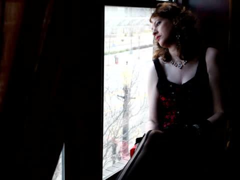 vidéos et rushes de femme assise à la fenêtre, toucher ses jambes flirter pour appareil - seulement des jeunes femmes