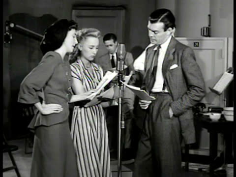 woman sitting knitting. radio studio: three actors standing at microphone w/ scripts in hand. love triangle younger woman in love w/ another woman's... - soap opera stock videos & royalty-free footage