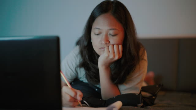 woman sitting making notes in a notepad and using laptop at home stock video - adult imitation stock videos & royalty-free footage