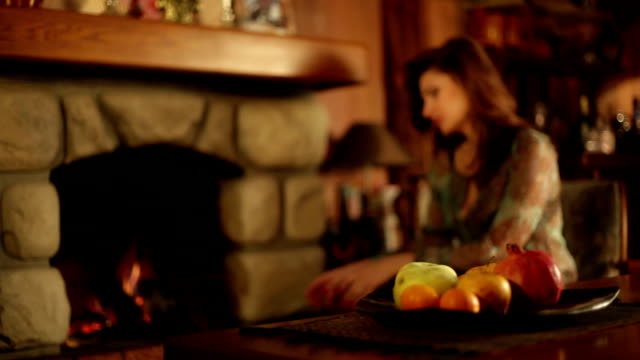 Woman sitting near fireplace stirs the flame