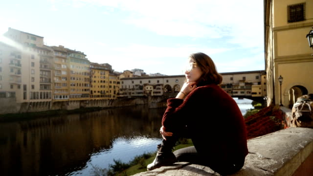 woman sitting near  ponte veccio and looking at view - florence italy stock videos & royalty-free footage