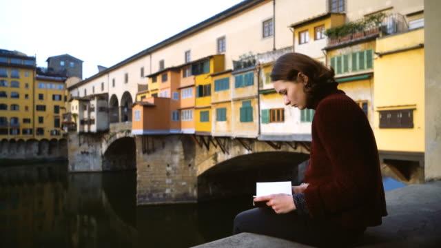 vídeos de stock e filmes b-roll de woman sitting near  ponte veccio and looking at view - florença