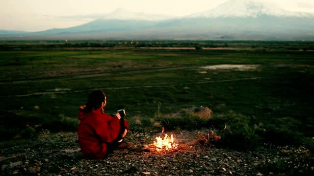 Woman sitting near the campfire near  Ararat
