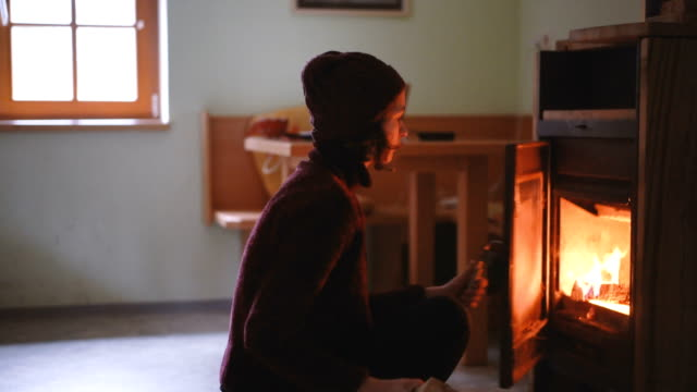 woman sitting near the fireplace - wood material stock videos & royalty-free footage