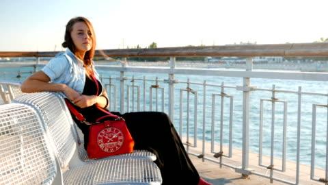 kvinnan som sitter nära havet är orolig och överväger, tänka på problem eller frågor - kommunikationsproblem bildbanksvideor och videomaterial från bakom kulisserna