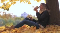 Woman Sitting Near Tree In Yellow Fall Leaves, Uses Apps And Drinking Coffee