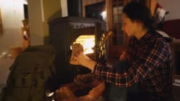 Woman sitting near wood stove  in cozy cabin