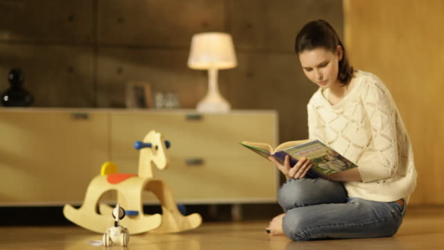 vidéos et rushes de woman sitting next to a rocking horse and reading a children's book on parquet floor in living room - parquet