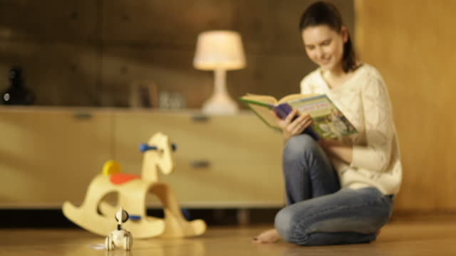 Woman sitting next to a rocking horse and reading a children's book on parquet floor in living room