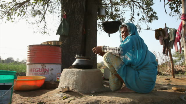 MS Woman sitting next to boiling pan / Rajasthan, India