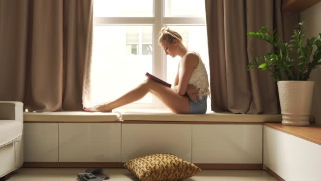 Frau sitzt neben Fenster arbeitet an tablet