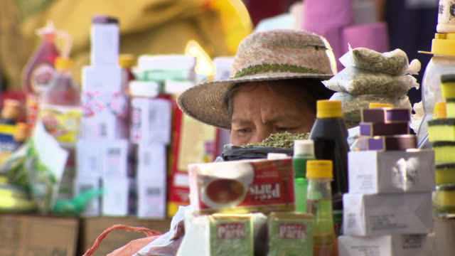 stockvideo's en b-roll-footage met woman sitting, obstructed view by various goods, la cancha market, cochabamba, bolivia - bolivia