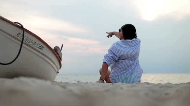 frau am strand sitzen, das leben genießen, spielen mit dem sand, strömen durch die hände - 35 39 years stock-videos und b-roll-filmmaterial