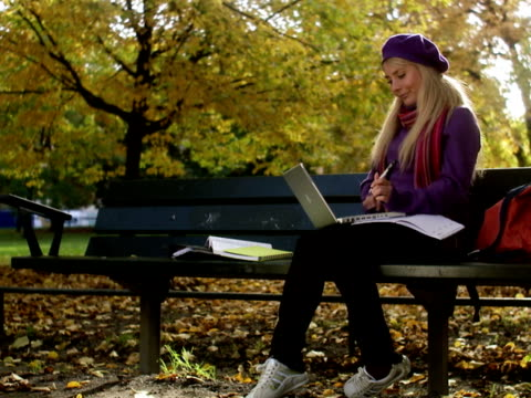 A woman sitting on a bench in a park using a laptop Stockholm Sweden.
