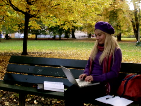 vídeos y material grabado en eventos de stock de a woman sitting on a bench in a park using a laptop stockholm sweden. - encuadre de tres cuartos