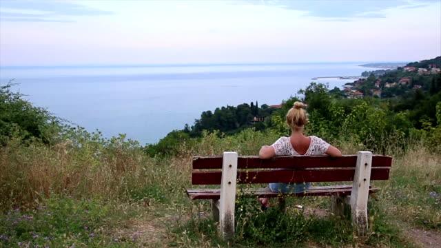 vídeos de stock e filmes b-roll de woman sitting on a bench looking at the sea - banco de parque