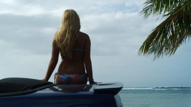 woman sitting on a car in a bikini - ビキニ点の映像素材/bロール
