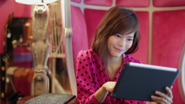 stockvideo's en b-roll-footage met ms woman sitting on a chair  using digital tablet - middellang haar