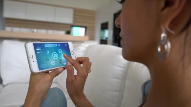 Vrouw zitten op een bank met behulp van een intelligente huis app