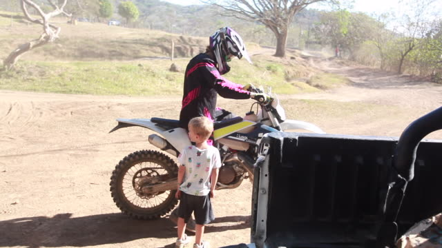 a woman sitting on a dirt bike starts the dirt bike and lifts a young boy onto it. - kelly mason videos stock videos & royalty-free footage