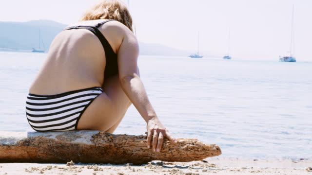 ms woman sitting on a log on the beach - bikini stock videos & royalty-free footage