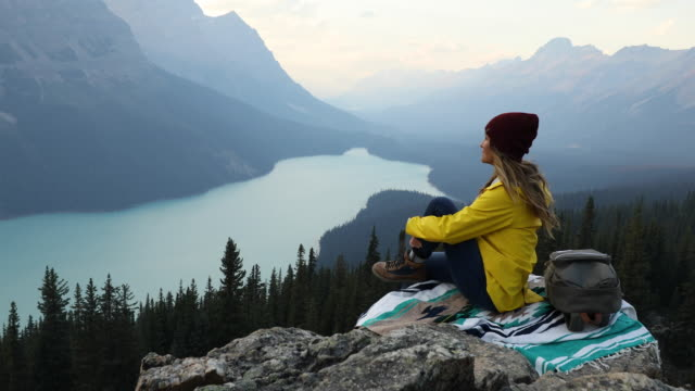 A woman sitting on a mountain top, taking in the view high above and alpine lake.